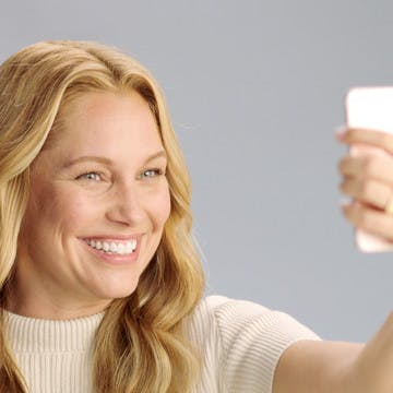 Image of blonde woman taking a selfie with her iPhone