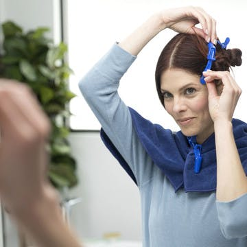 Image of woman sectioning her hair per her personalized instructions to avoid hot roots in bathroom
