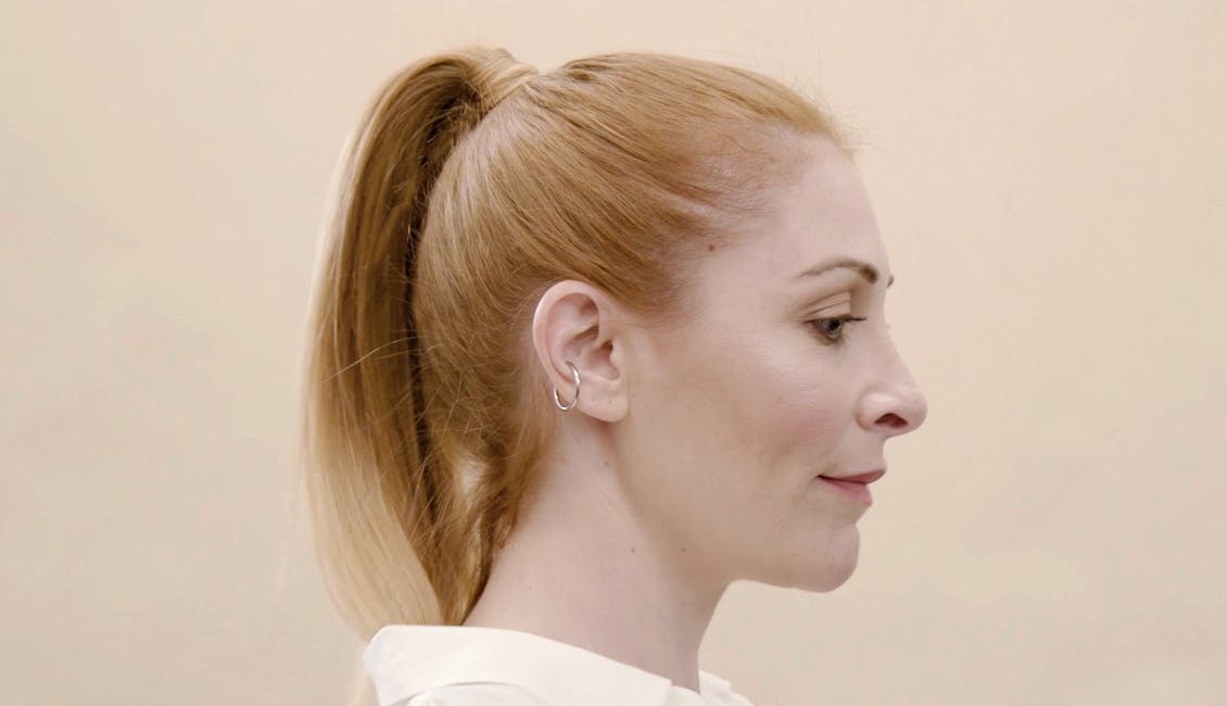 Image of esalon colorist with rich copper hair color and hair in a chic ponytail.