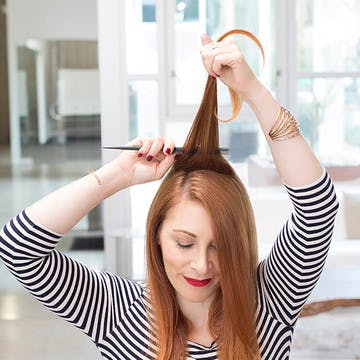 Image of woman gently teasing her custom hair color without damage using a fine-toothed comb