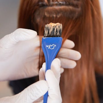 Image of someone with gloved hands and a an eSalon tint brush with hair color on it applying color to someone else's hair