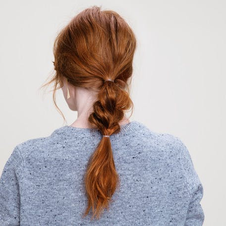 Image of esalon client Dominique's low Bohemian braid with dimensional copper hair color