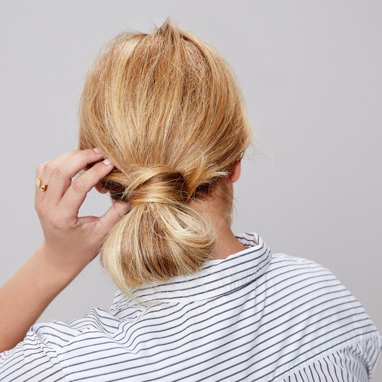 Image of esalon client renee's back of head shot with blonde hair and highlights in a low wrap-around bun updo in this how to article featured in color mastery