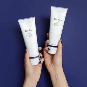 Image of hands holding two bottles of eSalon's Tint Rinse to enhance or neutralize hair color.