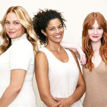 Image of three women with different skin tones and flattering custom hair colors for inspiration. The woman on the left has a light skin tone with a champagne blonde hair color, woman in the middle has medium skin with dark brunette hair color, and woman on the right has very light skin with red copper hair color
