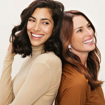 Image of two women laughing back to back, playing with their hair