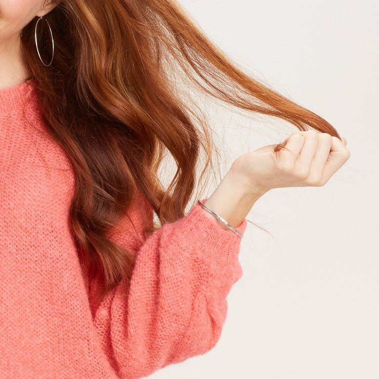 Image of woman holding a piece of her hair colored with esalon custom color and custom ends refresher