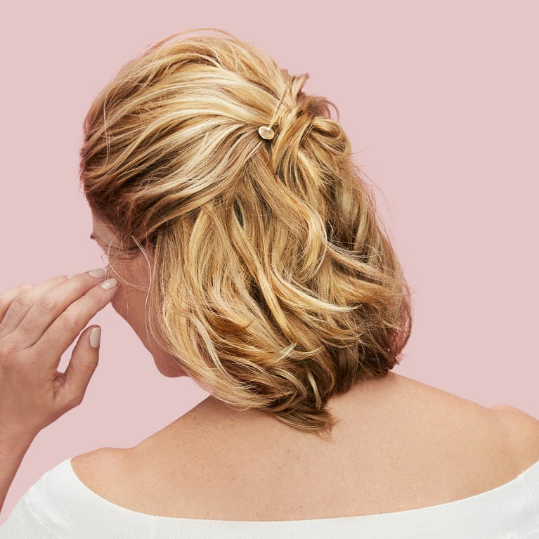 Image of esalon client victoria's back of head with blonde hair and highlights in a half-up-half-down easy updo with beautiful gold pins to hold hair as hero image in how to article featured on color mastery
