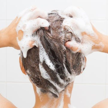 Image of woman in the shower washing her color-treated hair.