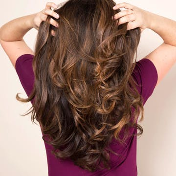 Image of woman running her hands through luscious, hydrated, healthy hair