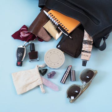 Carousel image of esalon employee handbags spilled over on a blue background to showcase beauty items inside