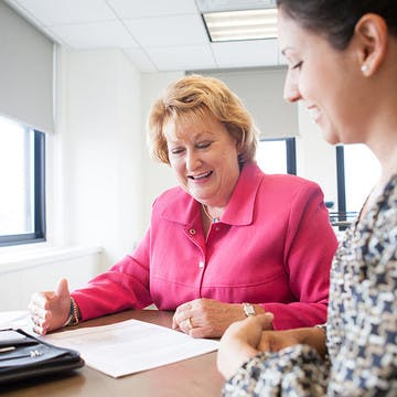 Image of CancerCare's CEO Patricia J. Goldsmith sitting at a desk with her employee looking over a document