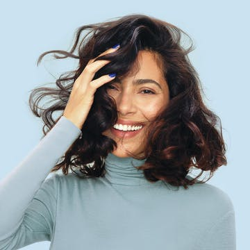 Image of woman looking thrilled with esalon custom hair color in brunette on a blue background and wearing a blue turtleneck