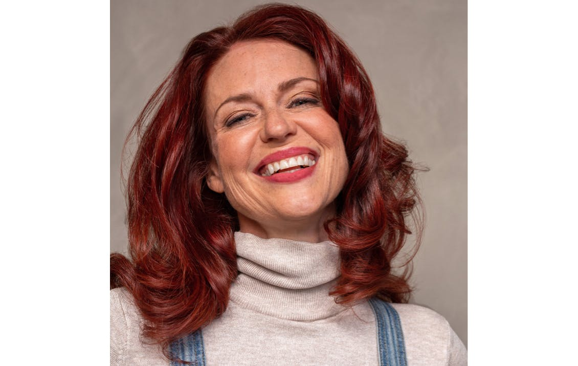 Image of esalon client with custom natural-looking red hair color to match skin tone and eye color