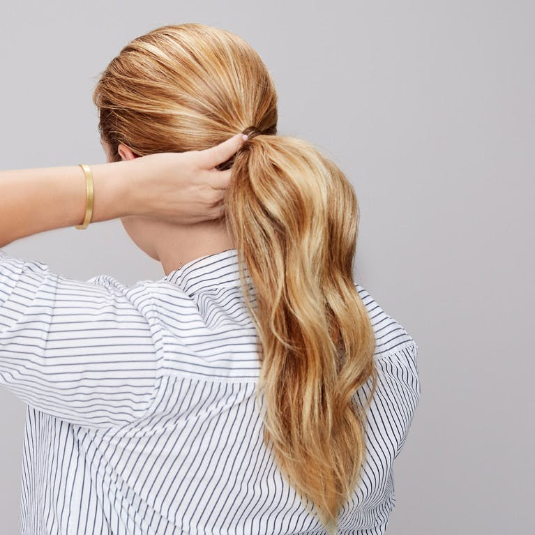 Image of esalon client renee's back of head shot with blonde hair and highlights in a sleek ponytail in this how to article featured in color mastery
