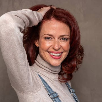 Woman in her 40s with esalon's custom red hair color to match her warm skin tone and eye color