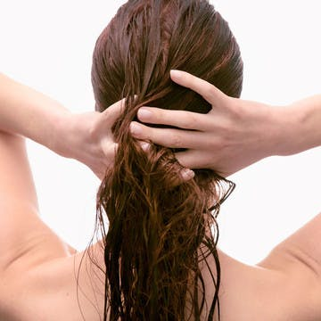 Image of woman's back of head in the shower washing her hair