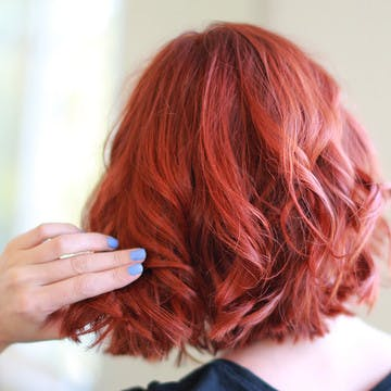 Woman with esalon's custom red hair color looking in mirror