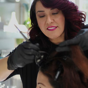 Image of esalon colorist Mindy working on a client's hair color in the Color Studio