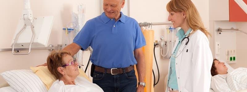 Médica e acompanhante conversando com paciente em quarto de hospital