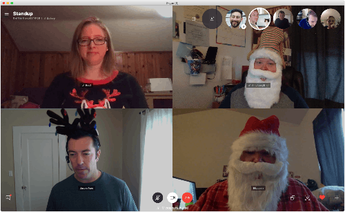 Stand-up meeting on Zoom with cameras on and people dressed up for holiday.