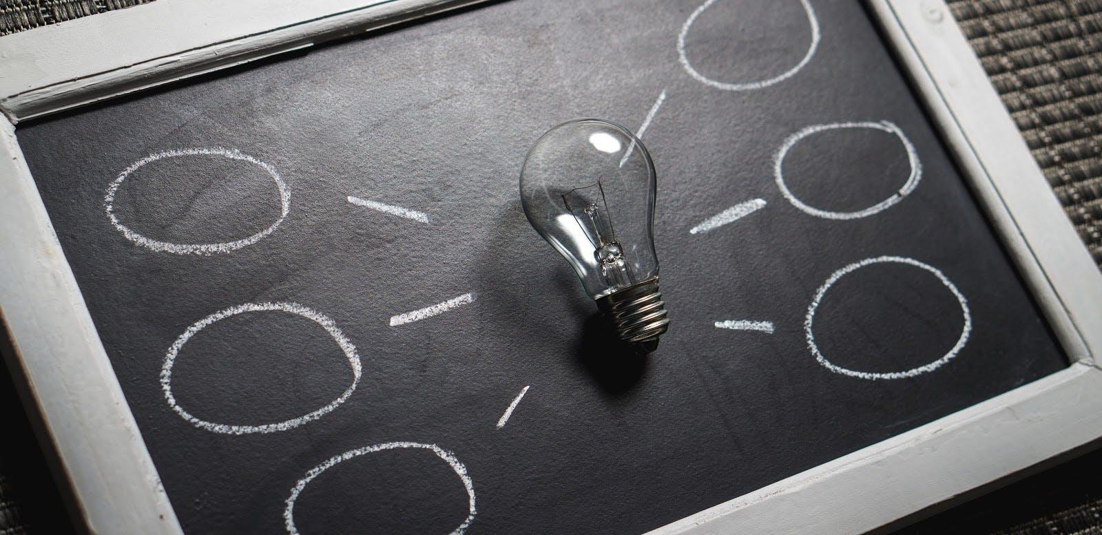 Framed chalkboard and a lightbulb.