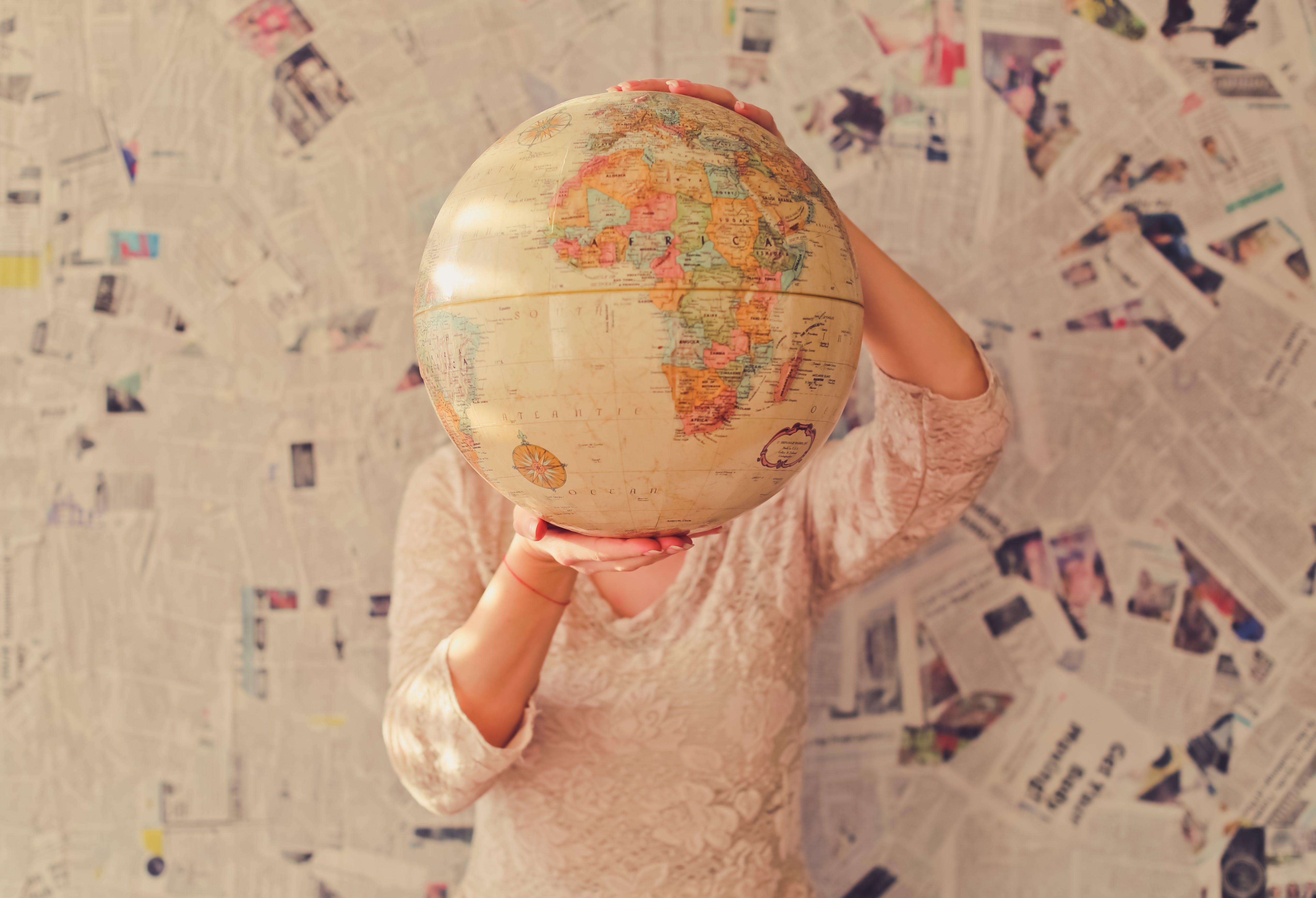 Person hält einen Globus vor ihrem Gesicht hoch.