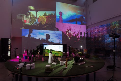 Round green table with various small statues, pots, books, white clay and a still screen of a grassy area scattered around surrounded by cameras. Behind it a projection of four wall-size images depicting the statues as silhouettes in front of grassy areas and plants.