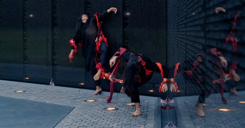 Two barefooted performers clad in black and connected through red ropes that tangle on their bodies, take different poses on the corner of a black wall with inscriptions on its surface.