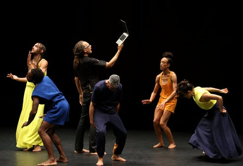 Six performers dressed in dark blue, yellow, and orange colors on a stage. Five of them move in various poses while the middle reads from an open laptop held upwards.
