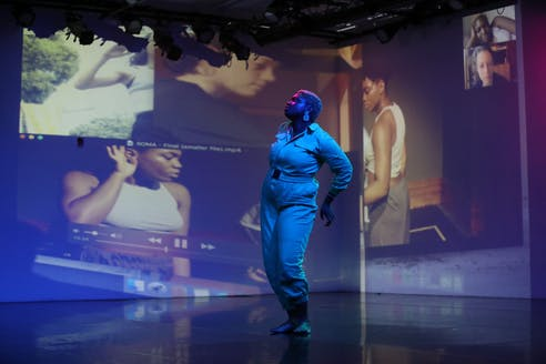 Ogemdi Ude, a performer dressed in a white jumpsuit stands sideways to the viewer looking upwards in the middle of a pink and blue illuminated stage. Behind Ude a video still collage of the same two figures in various angles is projected.