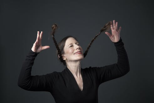 Portrait of Meredith Monk dressed in a black long-sleeved shirt, golden earrings and red lipstick – smiling while flipping with her raised arms the two low pigtail braids upwards.