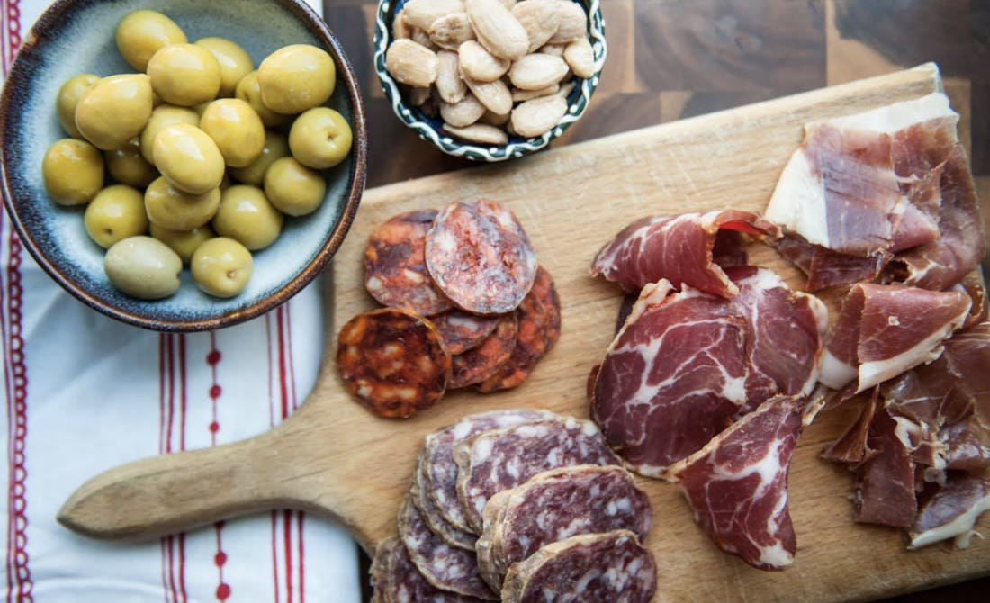 Selection of traditional Spanish tapas including a bowl of green olives and cured meats arranged on a wooden board