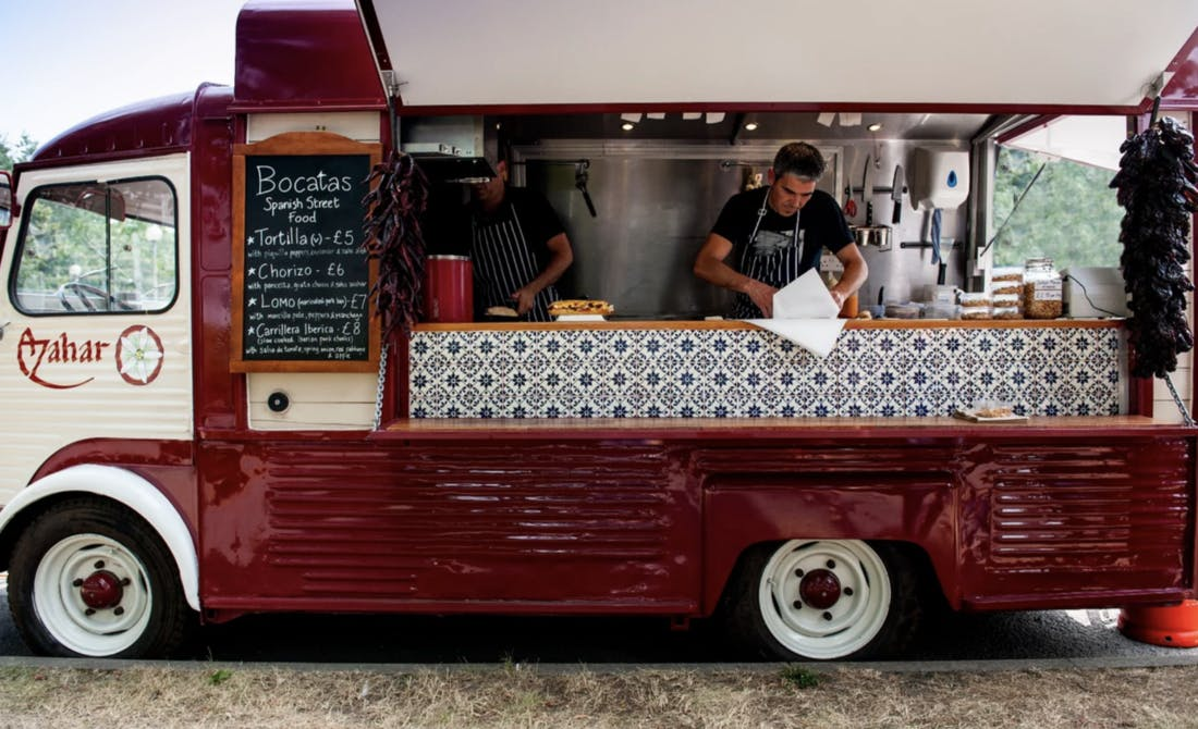 chef standing inside a Spanish street food truck whilst prepping food