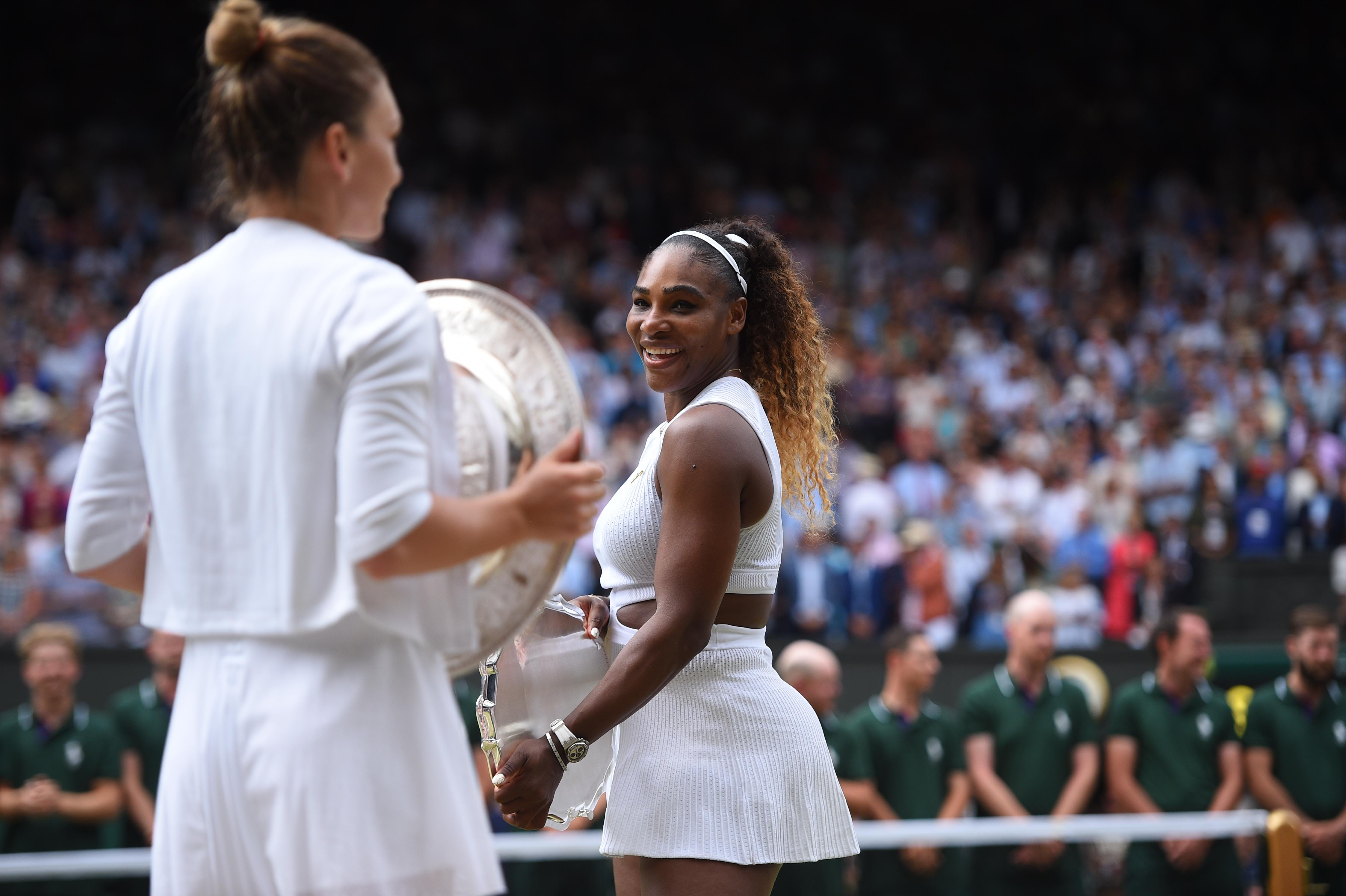 Serena Williams  looking smiling at Simona Halep and her Wimbledon 2019 trophy.