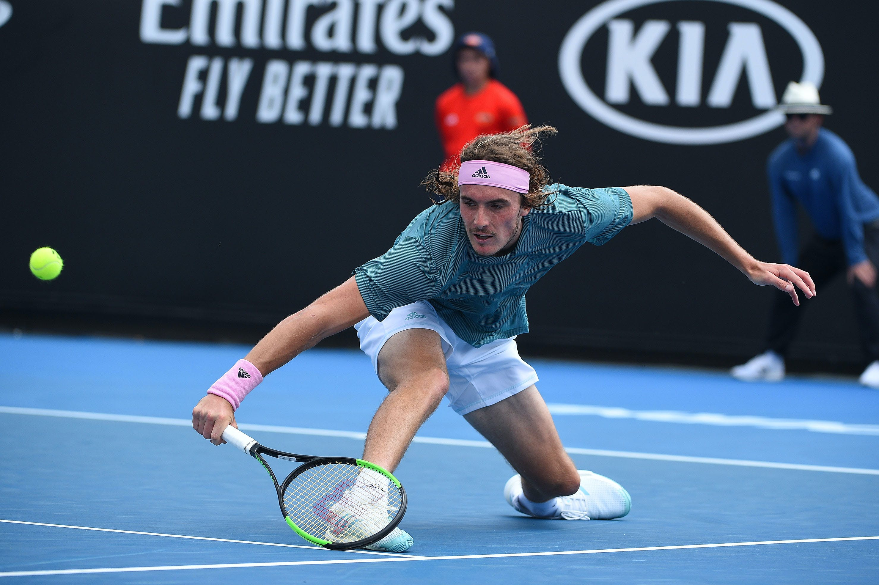 Stefanos Tsitsipas sliding for a drop shot backhand at the Australian Open 2019