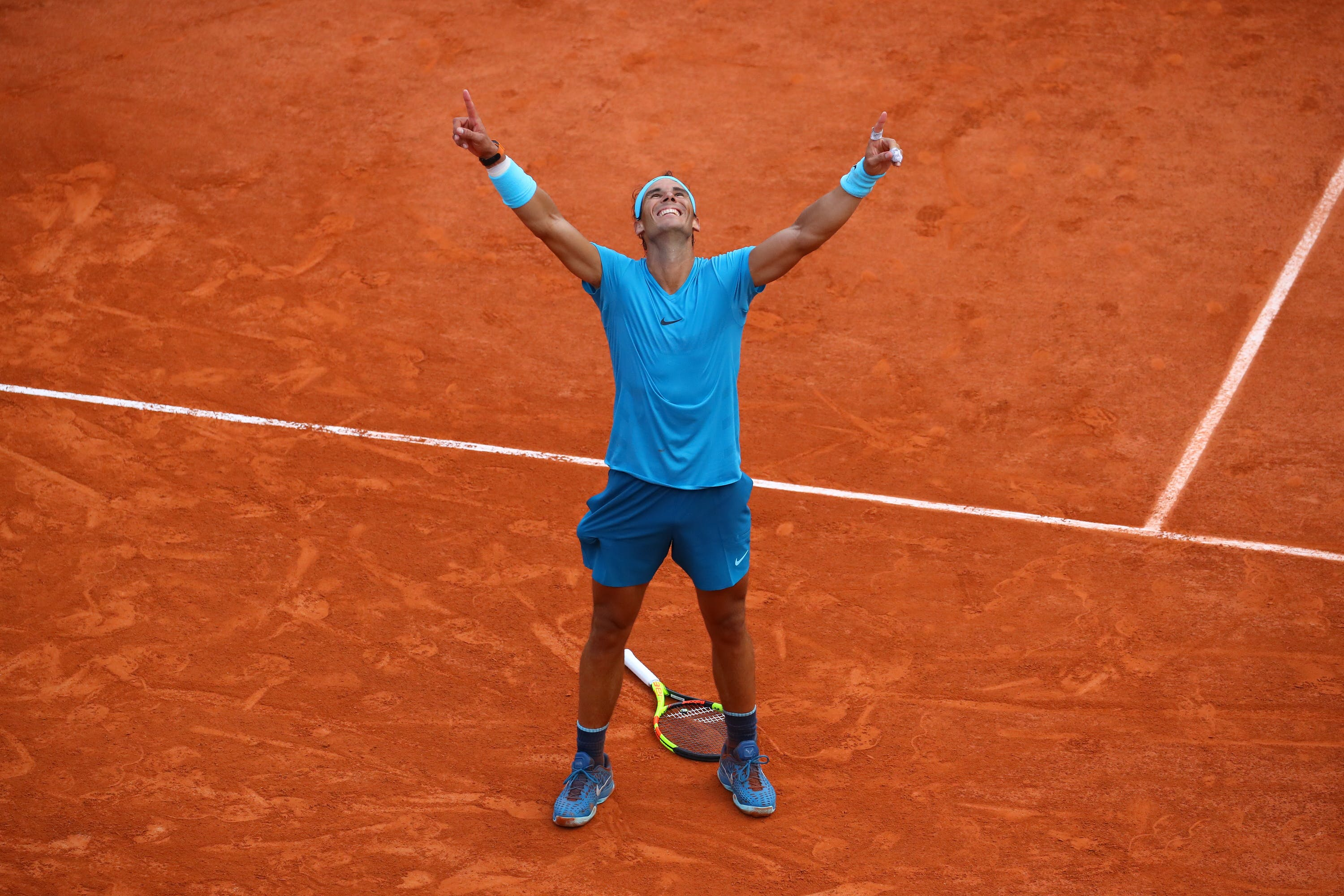 Rafael Nadal smiling and pointing the fingers to the sky as he wins Roland-Garros 2018
