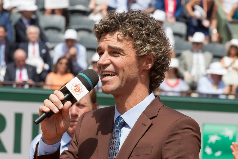 Gustavo Kuerten talking and smiling during a ceremony at Roland-Garros 2017