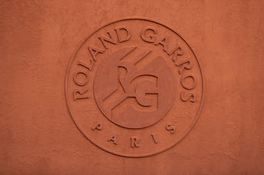 The Roland-Garros logo on the clay wall
