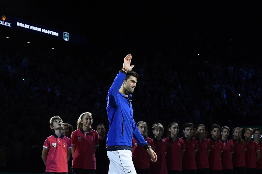 Novak Djokovic wawing to the crowd in front of the ball kids at the Rolex Paris Masters 2019
