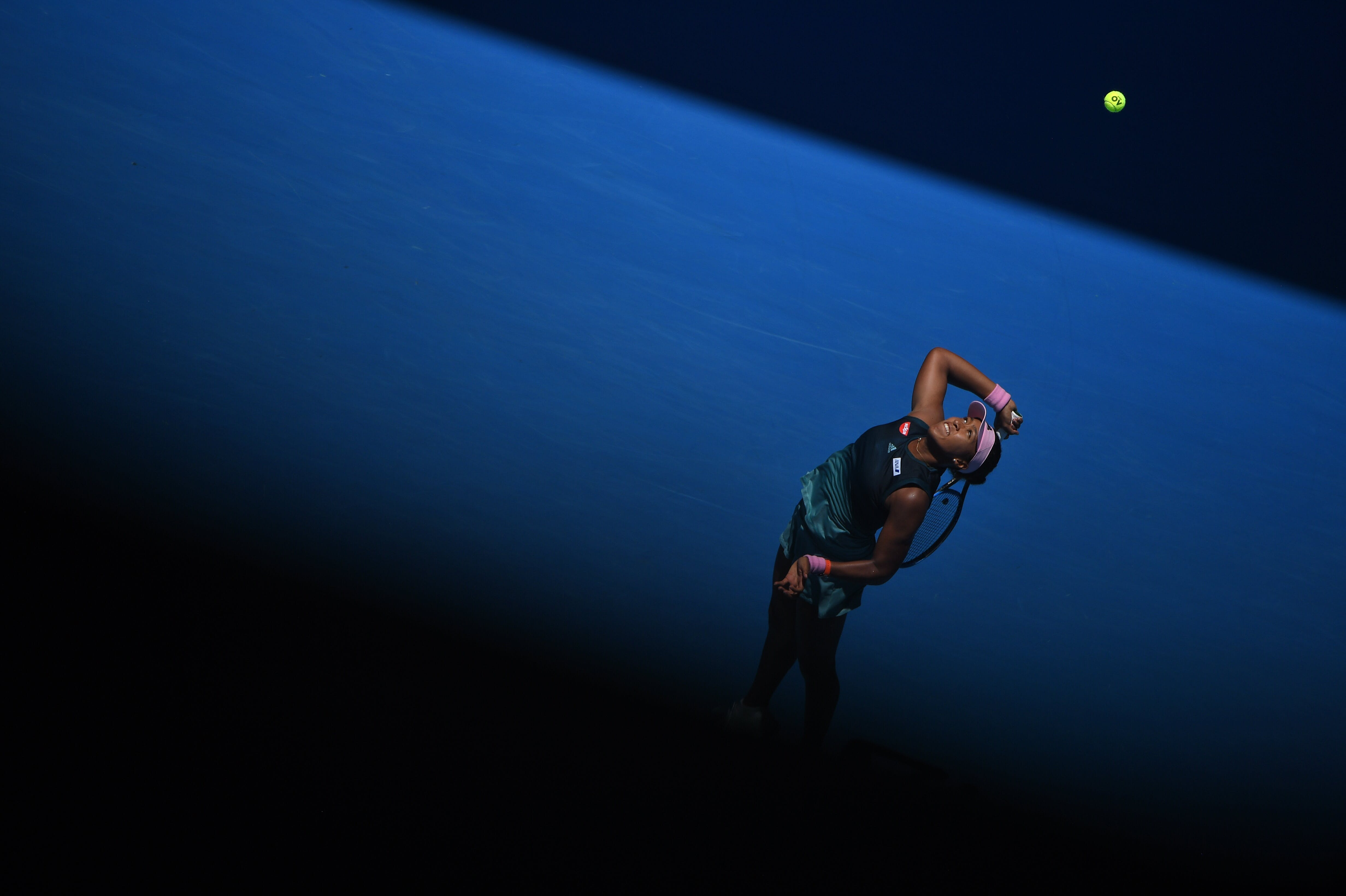 Naomi Osaka serving in the shadow during the Australian Open 2019