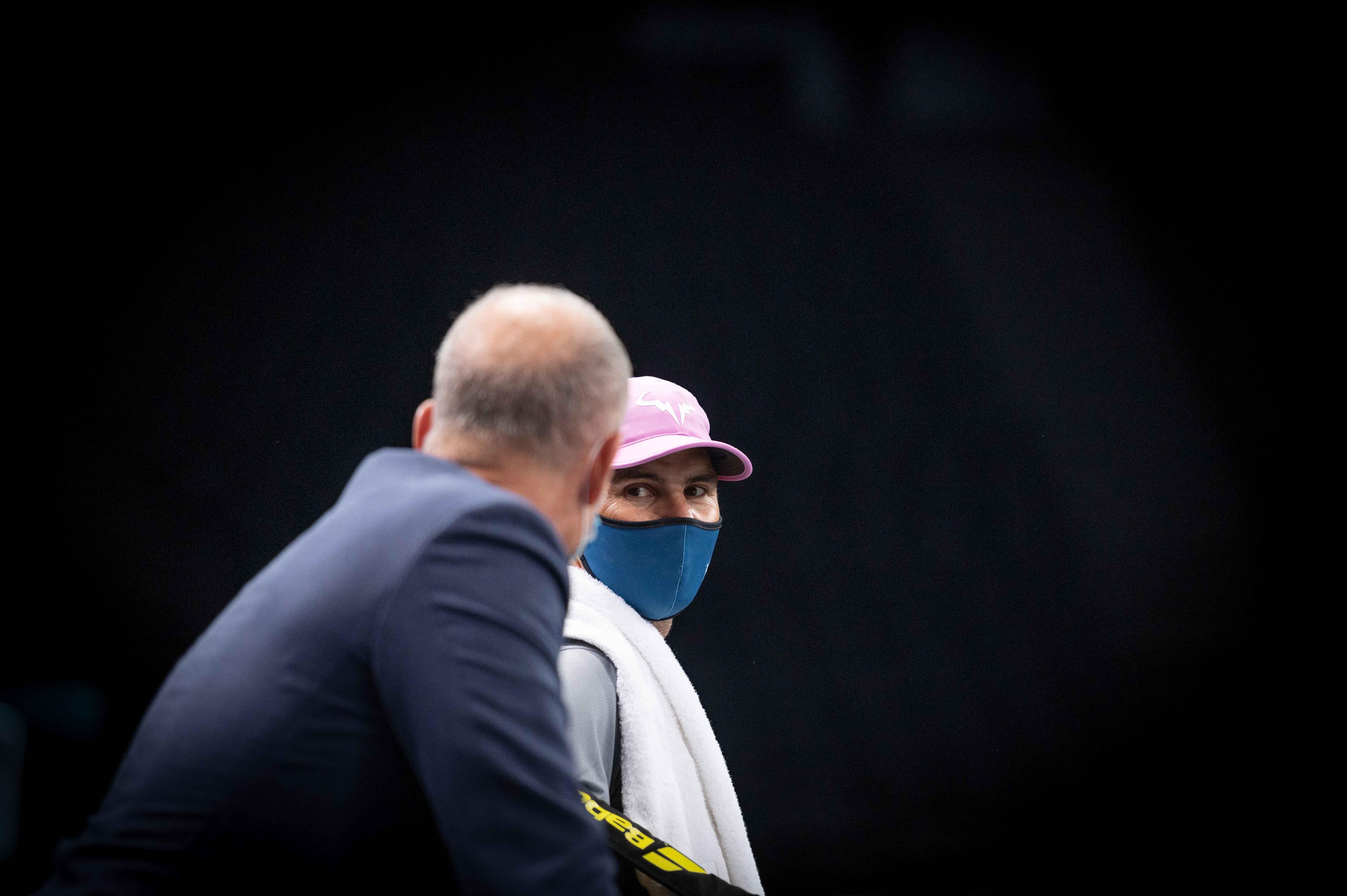 Rafael Nadal sourit derrière son masque en pleine discussion avec Guy Forget au Rolex Paris Masters 2020.