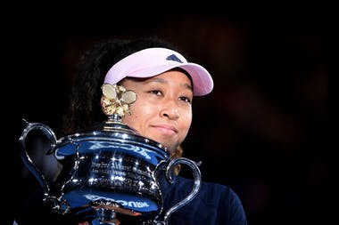 Naomi Osaka psing in the light and smiling with her 2019 Australian Open trophy