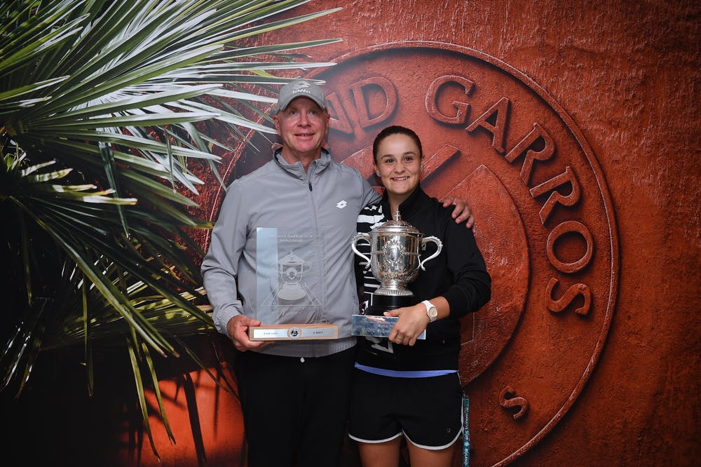 Craig Tyzzer and Ashleigh Barty posing with the 2019 Roland-Garros trophy.
