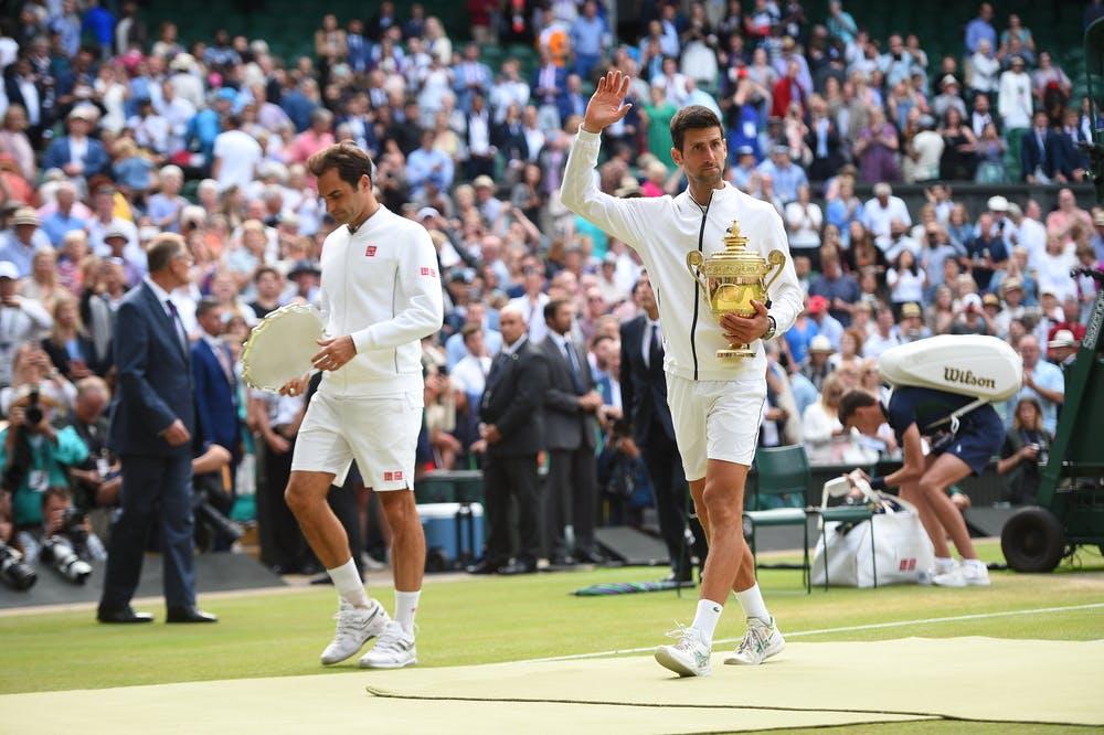 Novak Djokovic walking next to Roger Federer both holding their trophies Wimbledon 2019