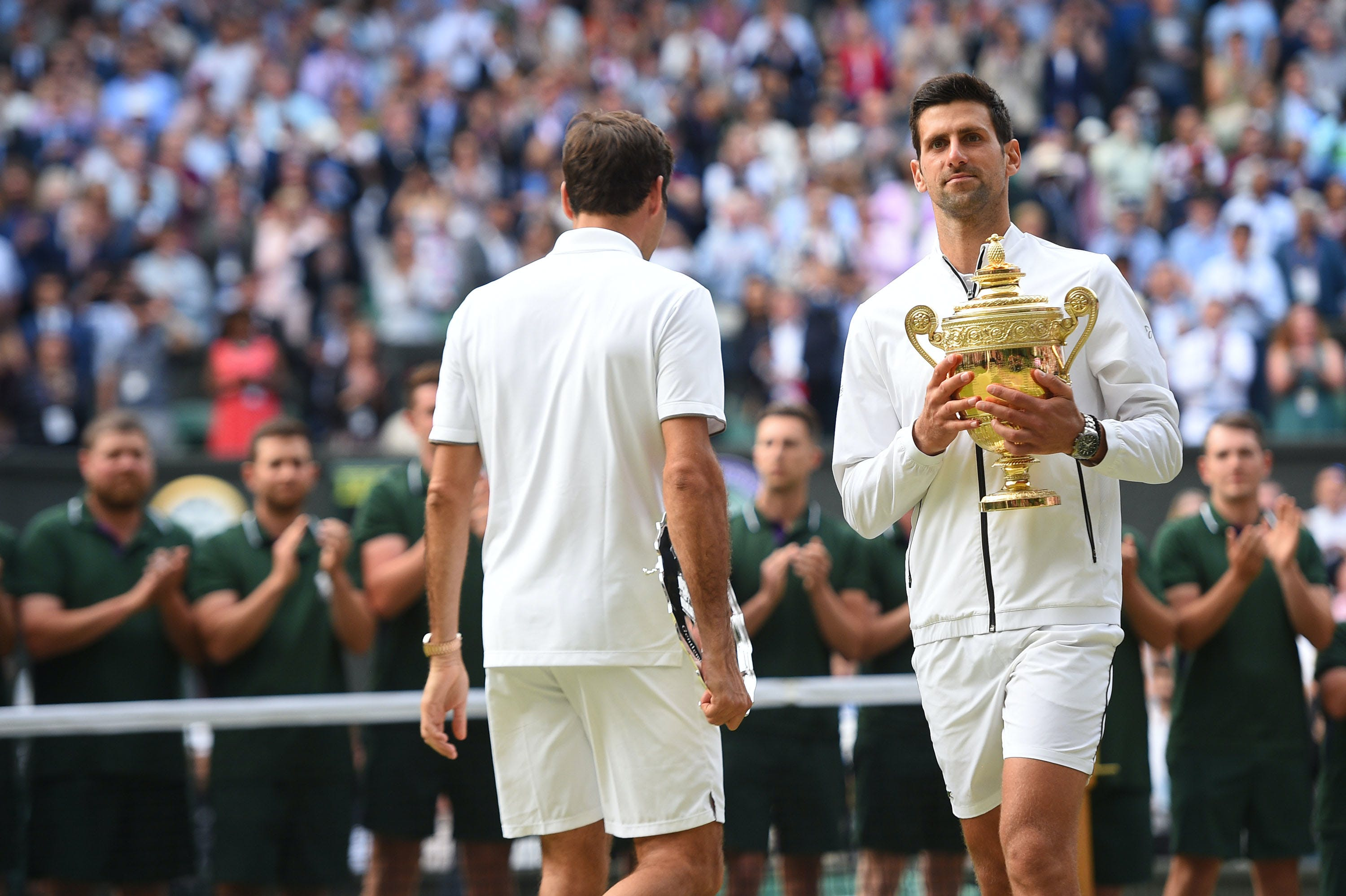 Novak Djokovic and Roger Federer changing ends after the trophy ceremony at Wimbledon 2019