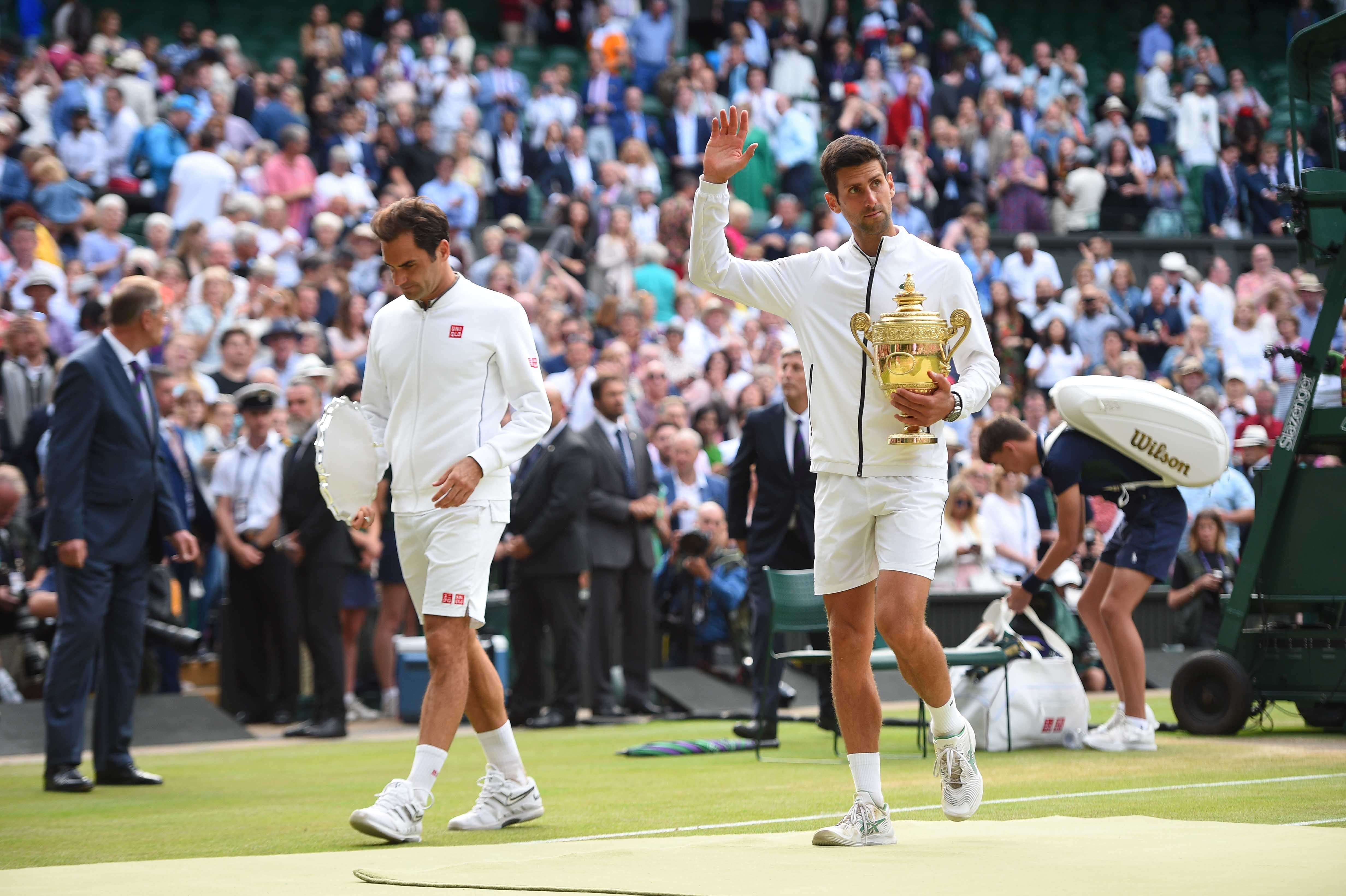 Novak Djokovic and Roger Federer walking with their trophies after the presentation at Wimbledon 2019