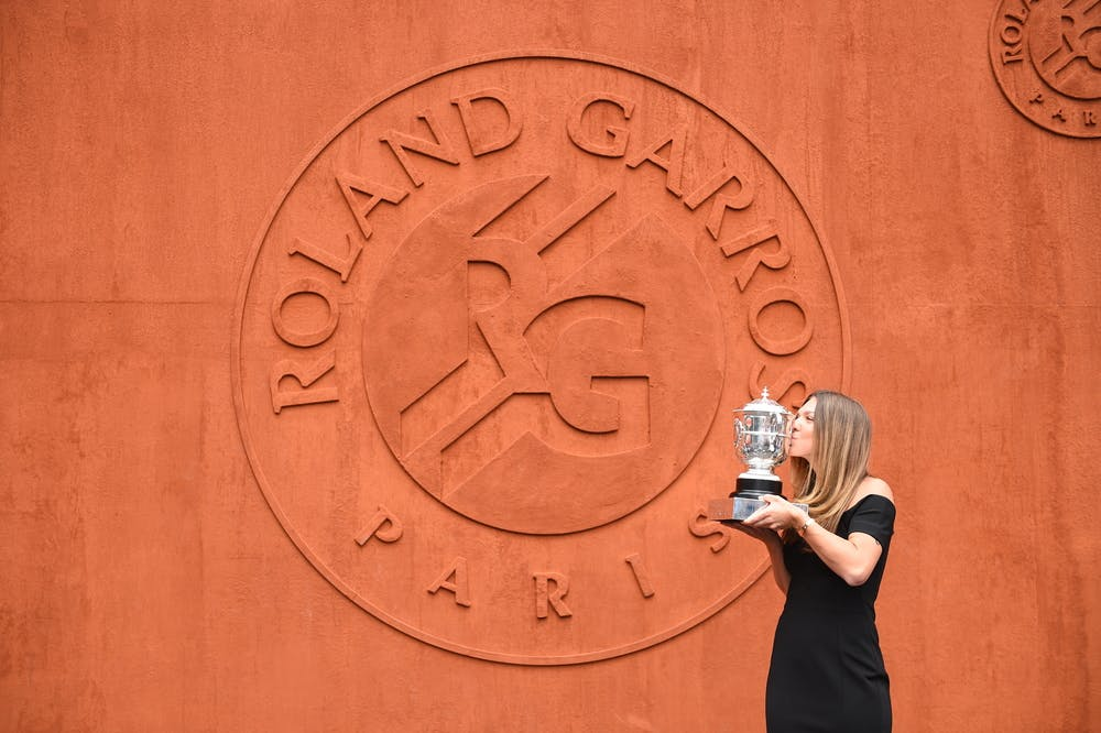 Simona Halep kissing the Roland-Garros 2018 trophy in front of the RG18 clay wall