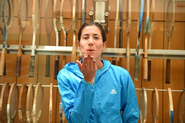 Garbine Muguruza smiling and kissing away the camera in front of vintage raquets at Roland-Garros
