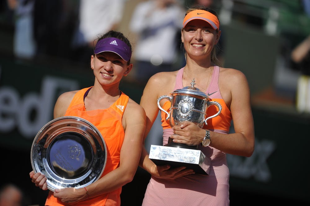 Maria Sharapova and Simona Halep posing with the 2014 Roland-Garros trophy